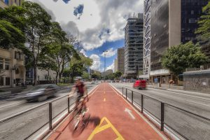 Red, protected bicycle lane in the middle of a six lane inner city road.